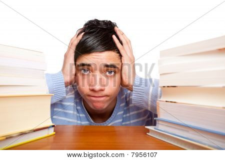 Young handsome student sitting on a desk between study books and looks frustrated.