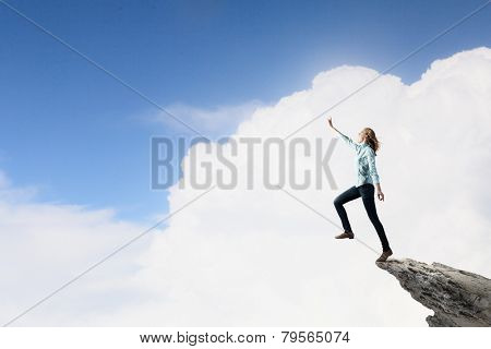 Young woman on rock edge making step above gap