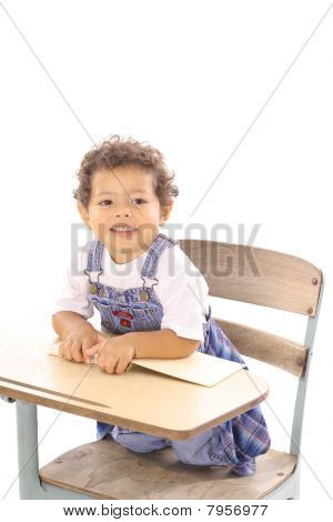 toddler with a book sitting in desk