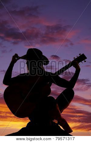 Silhouette Of A Woman With A Guitar Sit Hand On Hat