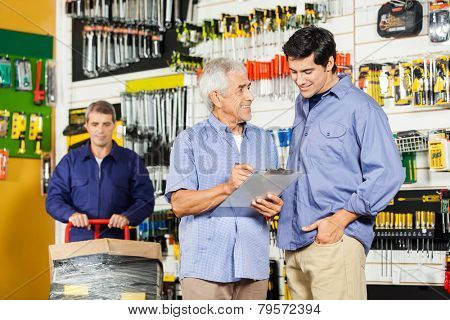 Father and son checking checklist on clipboard while worker working in background at hardware store