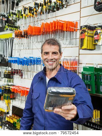 Portrait of confident worker offering packed product in hardware store