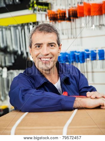 Portrait of happy mature worker leaning on tool package in hardware shop