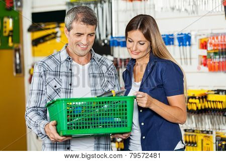 Happy couple carrying basket full of tools in hardware store
