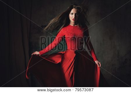 Sexy young lady in fluttering red dress