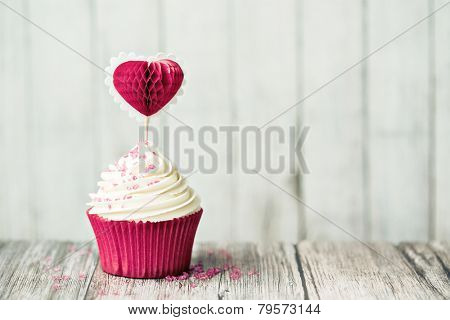 Cupcake decorated with a heart shaped cake pick