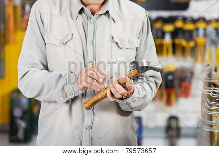 Midsection of mature man scanning hammer through smartphone in hardware store