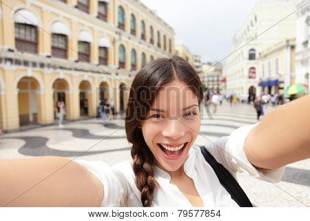 Selfie woman taking fun selfportrait in Macau, China in Senado Square or Senate Square. Asian girl tourist using smart phone camera to take photo while traveling in Macau. Travel and tourism concept.