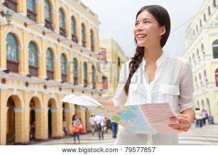 Tourist holding travel map in Macau. Woman visiting Macau, China for sightseeing looking for directions at tourists map smiling happy on Senado Square or Senate Square.