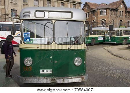 Lady enters old trolleybus in Valparaiso, Chile