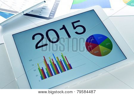 different charts with the economic forecast for 2015 in a tablet, on a desk full of charts