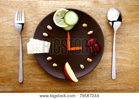 Fruits, vegetables, nuts and crackers on a plate arranged like a clock