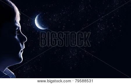 Cute boy of school age against night background