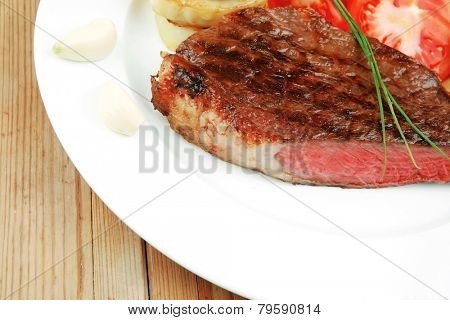 meat savory : grilled beef fillet mignon on white plate with tomatoes , potatoes and chives on wooden table