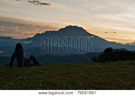 Unidentified Woman Taking A Rest On The Grass With Mount Kinabalu As Background