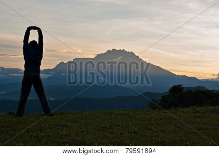 Unidentified Woman Stretching At The Outdoor With Mount Kinabalu As Background