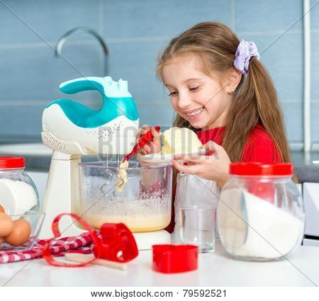 preparing cookies to valentine's day. little girl adds butter to the dough for cookies