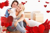 picture of fiance  - Woman sitting with her fiance giving keys against love heart pattern - JPG