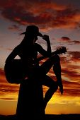 pic of redneck  - A silhouette of a cowgirl wearing her hat and playing her guitar - JPG