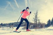 picture of country girl  - Woman cross country skiing on a yellow skis - JPG