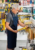 image of hardware  - Side view of senior salesperson working in hardware store - JPG