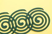 stock photo of mosquito repellent  - closeup of green mosquito coil on yellow background - JPG
