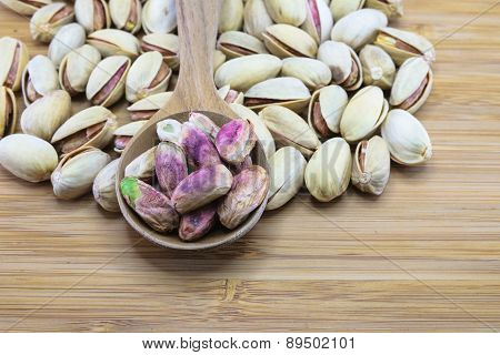Pistachio Nuts In Wood Spoon On Wood Background