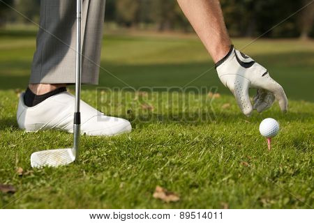 Person positioning golf ball on tee