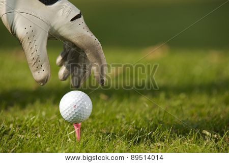 Human hand positioning golf ball on tee, close-up