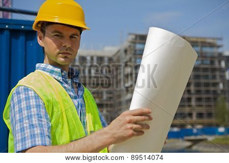 Portrait of engineer holding blueprint at construction site