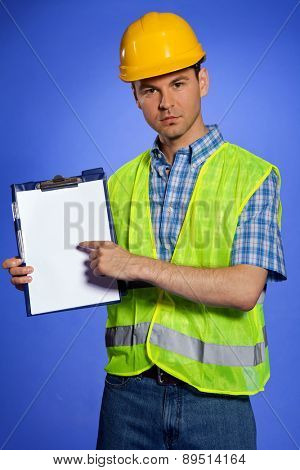 Portrait of architect in coveralls and hardhat pointing at clipboard