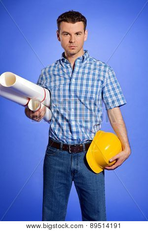Portrait of architect holding blueprint and hardhat