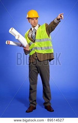 Businessman in coveralls holding blueprint and pointing