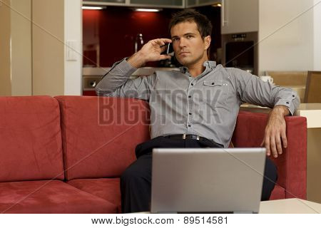 Young man using mobile phone in front of laptop