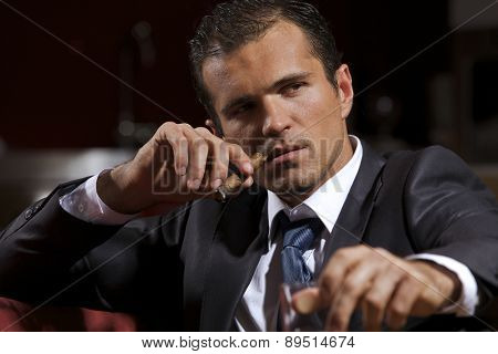 Young man smoking cigar and holding whisky glass