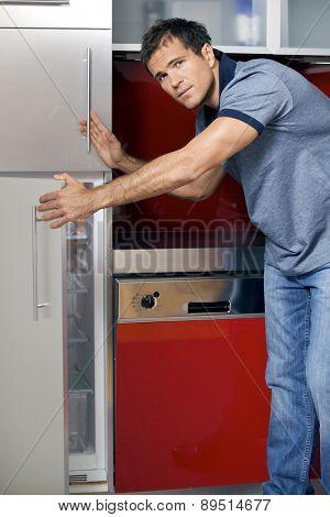 Portrait of young man opening door of refrigerator