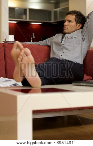 Young man sitting in sofa with hands behind head