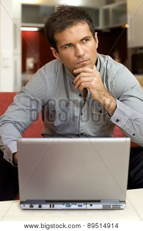 Young man with laptop, hand on chin