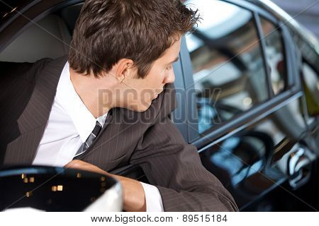 Young man sitting in new car