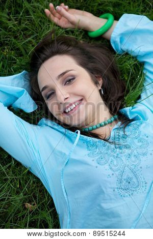 Portrait of young woman lying on grass
