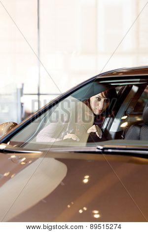 Young woman looking at new car