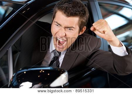 Angry young man clenching his fist, sitting in new car and shouting