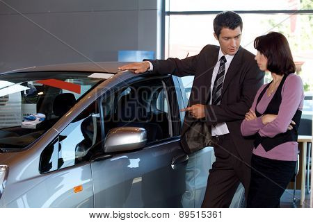Car salesman explaining car features to customer
