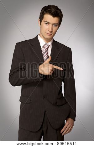 Young caucasian businessman pointing his finger right
