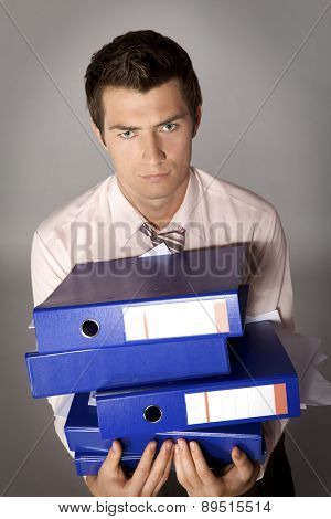 Young caucasian businessman holding a stack of binders