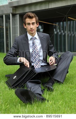 young caucasian businessman sitting on grass with documents