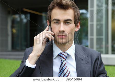 young caucasian businessman sitting on grass