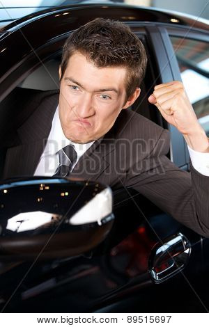 Angry young man clenching his fist, sitting in new car