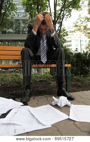 young caucasian depressed businessman in park
