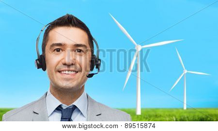 business, people, technology, alternative energy and development concept - smiling businessman in headset